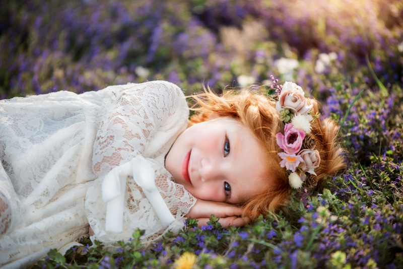 NE Family Photographer, little girl with flower crown laying in a field of flowers