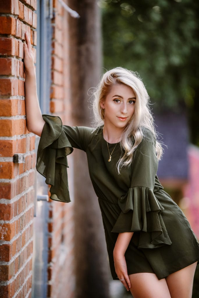 NE Family Photographer, young woman posing against a brick wall