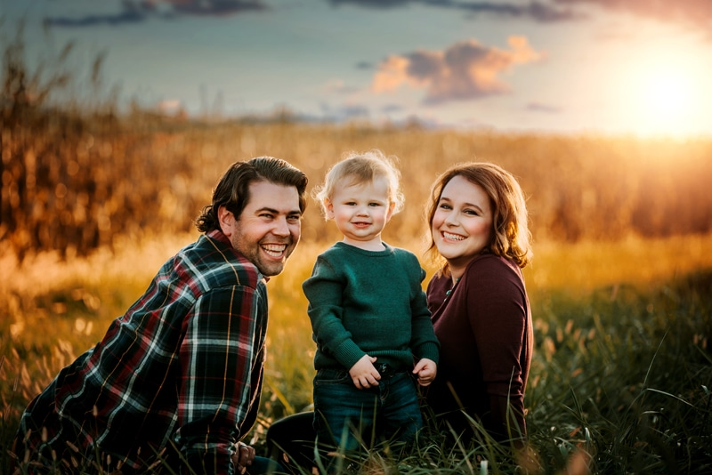 NE Family Photographer, family of three sitting together in a field at sunset